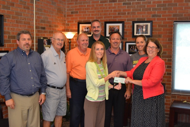 Sarah Wilson, representing the Fishing River Running Club, presented a $1,000 check to board president Molly McGovern and other members of the Excelsior Springs Educational Foundation. The money was raised at the Waterfest 5K and will be used by the foundation to support teachers and students with funds outside the district's regular budget. ES Educational Foundation board members include (from left) Tray Harkins, Larry Greim, Bill Griffey II, Brian Rice, Mike Anderson and Terri Irons.